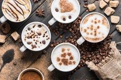 Чашки кофе, кофейные зерна, печенья и специи на таблице Стоковое Фото