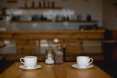 Чашки кофе на таблице в кафе стоковые изображения rf