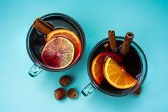 2 чашки обдумыванных гаек вина на голубой предпосылке Плоское положение стоковое фото