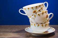 Чашки одно на другом на голубой предпосылке Стоковое Фото