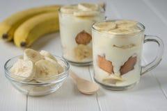 2 чашки пудинга банана и ломти банана в стеклянном шаре на белой таблице Стоковое Изображение