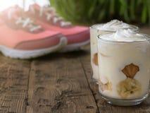 2 чашки пудинга банана с сливк и тапками на заднем плане на деревянном поле Стоковые Фото
