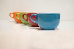 4 чашки различной стойки цветков в ряд Стоковое Фото