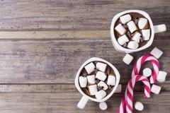 2 чашки с горячим шоколадом и зефиром на затрапезном деревянном столе Стоковая Фотография RF