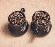 2 чашки с зернами кофе на деревянной предпосылке Стоковые Изображения