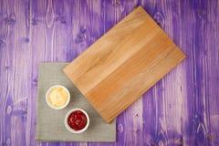Чашки с кетчуп и сыром на салфетке сделанной от холста на деревянном столе Стоковое фото RF