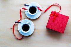 Чашки с кофе, подарочной коробкой украшенной лентой на таблице Стоковые Фотографии RF