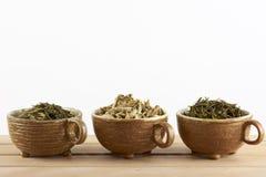 3 чашки с листьями зеленого чая на белой предпосылке Стоковые Изображения RF