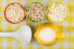 Чашки с овсом, рожью, хлопьями ячменя, молоком кувшина и ложкой Стоковое Фото