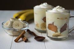 2 чашки с пудингом банана, кусками банана и циннамоном на белом деревянном столе Стоковая Фотография
