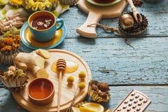 Чашки с травяным чаем и частями лимона, высушенных трав и различных украшений Стоковое Фото