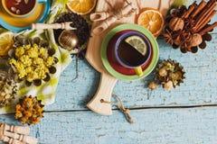 Чашки с травяным чаем и частями лимона, высушенных трав и различных украшений Стоковое Изображение