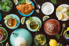 Чашки травяного чая с листьями лимона и мяты, корня имбиря и круассана на деревянной предпосылке, взгляд сверху Стоковые Фото