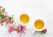 2 чашки чаю и ветви малых розовых роз стоковые фото