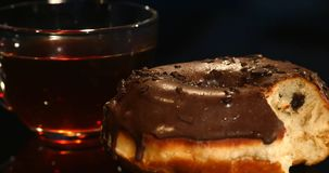 Чашки чаю и donuts шоколада на черной предпосылке Стоковые Изображения