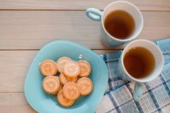 2 чашки чаю на голубой салфетке Печенья на голубой плите на деревянной предпосылке Стоковое фото RF