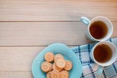 2 чашки чаю на голубой салфетке Печенья на голубой плите на деревянной предпосылке Стоковые Фотографии RF