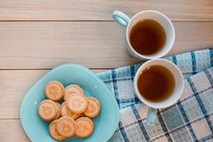 2 чашки чаю на голубой салфетке Печенья на голубой плите на деревянной предпосылке Стоковая Фотография