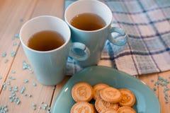 2 чашки чаю на голубой салфетке Печенья на голубой плите на деревянной предпосылке Стоковая Фотография RF