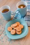 2 чашки чаю на голубой салфетке Печенья на голубой плите на деревянной предпосылке Стоковое Фото