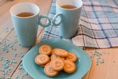 2 чашки чаю на голубой салфетке Печенья на голубой плите на деревянной предпосылке Стоковое Изображение