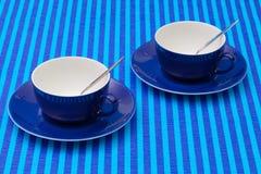Чашки чаю расположения симметрии пустые на голубом striped tableclo Стоковое Фото