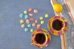 2 чашки чаю с красочными меренгами на голубой предпосылке Стоковое Фото