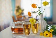 2 чашки чая ноготк calendula на таблице, с свежими цветками indoors стоковое фото rf