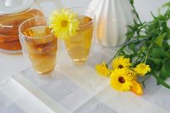 2 чашки чая ноготк calendula на таблице, с свежими цветками indoors стоковая фотография rf