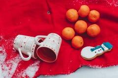Чашки ornaiment рождества красные белые - натюрморт рождества Апельсины и пряник снеговика на красном заволакивании Стоковое Изображение RF