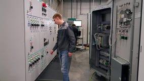 Чебоксар, республика Chuvash, 5-ое марта 2019 Работник идет к шкафу контроля и переключает тумблер сток-видео