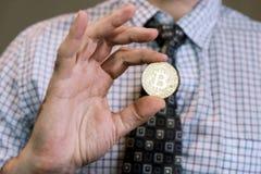 Чеканенный знак внимания Bitcoin золота в руке Стоковые Фото