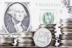 Чеканьте рубль на предпосылке стогов банкноты и денег доллара Стоковая Фотография RF