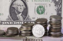 Чеканьте рубль на предпосылке стогов банкноты и денег доллара Стоковые Фотографии RF