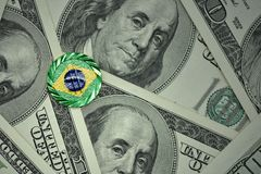 чеканьте с знаком доллара с национальным флагом Бразилии на предпосылке банкнот денег доллара Стоковое Фото