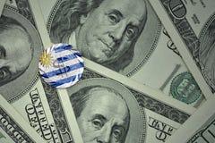 чеканьте с знаком доллара с национальным флагом Уругвая на предпосылке банкнот денег доллара Стоковые Изображения RF