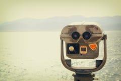 Чеканьте эксплуатируемого телезрителя биноклей перед ландшафтом моря Стоковые Изображения RF