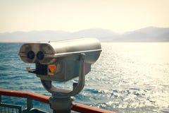 Чеканьте эксплуатируемого телезрителя биноклей перед ландшафтом моря Стоковые Фото