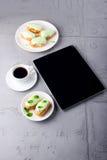 Чеканьте eclairs на плите, кофе и цифровой таблетке с белым sc Стоковое Фото