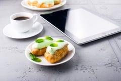 Чеканьте eclairs на плите, кофе и цифровой таблетке Стоковые Изображения RF