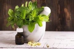 Чеканьте sprigs, масло пипермента и пилюльки над деревянным столом Стоковая Фотография
