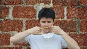 Человек Азии молодой носит маску N95 для для защиты плохого загрязнения PM2 пыль 5 с предпосылкой кирпича видеоматериал