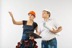 Человек архитектора нося светокопии женщины трудной шляпы или построителя шлема и сотрудника рассматривая стоковое фото rf