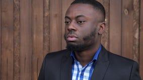 Человек Афро американский в костюме поворачивает gead и усмехаться видеоматериал