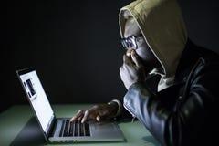 Человек Афро американский сидит на ноче на столе компьютера используя интернет Ноча занимаясь серфингом на интернете Gamer сидит  стоковые изображения