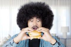 Человек Афро есть большой cheeseburger дома Стоковое Изображение RF