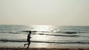 Человек бегуна спортсмена студента силуэта туристский молодой с подходящей сильной тренировкой тела на красивом песке пляжа заход сток-видео