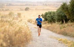 Человек бежать на заходе солнца на майне проселочной дороги стоковое изображение rf