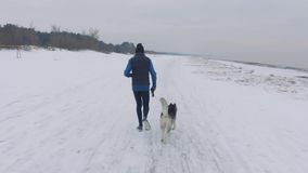 Человек бежать на снежном пляже с собакой