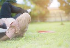 Человек битника азиатский лежа на зеленой траве и ослабляя для того чтобы слушать музыка белым беруш от компьтер-книжки пока его  Стоковое Изображение RF
